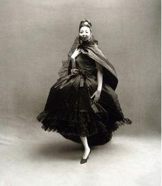 China Machado in Dior's airiest silk dress with lace ruffles worn with black taffeta stole, photo by Avedon, Paris studio, August 1959