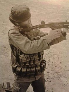 "A Vietnamese ""Mike Force"" member test-fires an Israeli-made Uzi submachine gun, probably a welcome replacement for his ancient M3 grease gun (bottom left)."