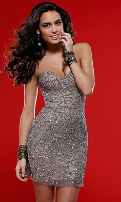 A mesmerizing pattern of shimmering sequins will have heads turning at your homecoming or next cocktail party. This fabulous sequined short dress by Scala featuring a strapless bodice with a sweetheart neckline and sheer overlay. A slim fitting short strapless dress available in Nude/Black or Dark Lead with a mini hemline