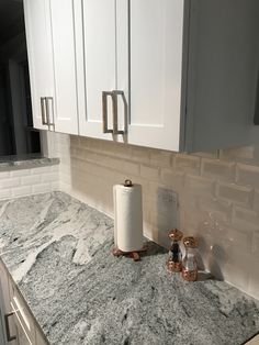 White shaker cabinets, stainless steel hardware, Silver Cloud granite, beveled white subway tile, copper accessories