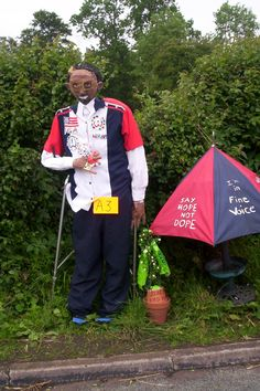 Wil-i-am scarecrow - complete with a Blackeyd peas pot plant and 'the Voice' umbrella.