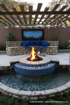2012 Garden World Spring Festival - Platinum Award. Mediterranean-inspired patio area with integrated fire pit and water feature.