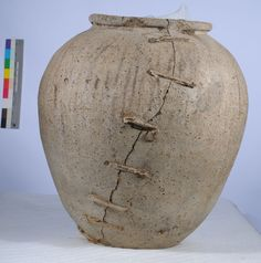 Roman storage pot, late 1st - early 2nd century AD, made in Britain of British clay. Unusually large, and though made from coarse clay, expensive to produce in its time, thus the lead staples added on in ancient times to repair the pot.