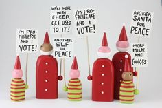 Picketing Santas and Elves by Hilary Pfeifer. These festive fellows are not afraid to stand up for what they believe! Each lighthearted figure is carved from wood and painted by hand. Each is unique and may vary. Sold separately or in a group of 6 as shown.