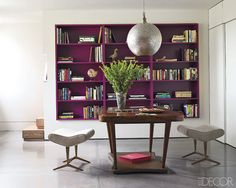 Bold purple bookcase with neutral/natural  colored walls and furniture. Nice!