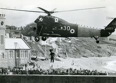 An old  photo of a helicopter conducting a Lifeboat Day display exercise at Porthleven harbour on 24 August 1979. From Helston Museum's photographic collection, Helston, Cornwall.