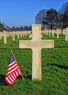 The American Flag honors the fallen at Normany.. Here rests in honored glory a comrade in arms known but to God.