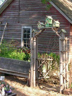 AN ARBOR MADE OFTHICK BRANCHES AND TOPPED WITH BIRDHOUSES.