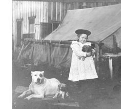 Miriam Kiehl holding a puppy outside of their home at Fort Lawton, Washington, ca. 1897 :: H. Ambrose Kiehl Photograph Collection