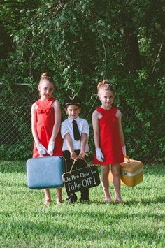 Have your ring bearer and flower girl carry signage that is travel-inspired! We especially adore how the girls are dressed as flight attendants and the boy is donning a precious pilot outfit. #TravelThemed #Wedding  Photo by Powell Pictures