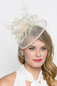 "Be the talk of the party in this beautiful fascinator! The round base is embellished with soft french netting, ribbon loops that bounce around the mesh centerpiece and topped off with soft fluffy feathers. Base comes attached to a headband and comfortably fits any adult head size. - 8"" Round Mesh Base - Easy Wear Headband - 'Tuck Away' Optional Birdcage Veil"