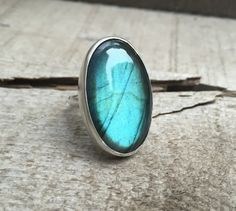 A stunningly luminescent bright blue green flashy labradorite makes this statement ring pop! This stone has been carefully set in sterling silver with a handmade ring band from sterling silver half do