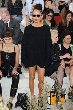 Zoe Kravitz wears a black sweaterdress, platform wedges, statement earrings, and cat-eye sunglasses