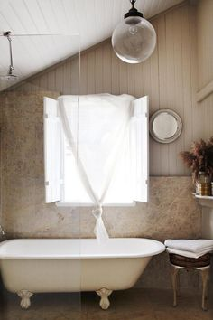 Stone squares. Claw foot tub behind glass. Window and shutters.