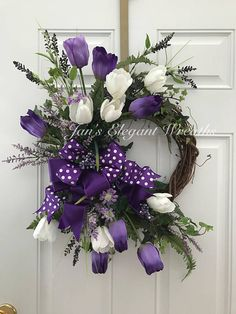 This is a Beautiful Spring Tulip Wreath for all of my purple lovers! Large Purple and White Tulips, purple heather, loads of foliage including ivy, ferns, and boxwood blossom out from a gorgeous double ribbon bow made of deep purple and purple polka dot ribbons. This beauty will