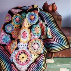 Create a 3D crochet blanket with crochet flowers and a rainbow granny square crochet design using Sue Pinner's pattern. This crocheted blanket looks stunning in a rainbow colourway with black yarn used for separating the coloured yarns.