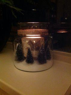 Kerstbomen in een glazen pot. Een houten waxinelichthouder in het midden en kunstsneeuw als bodembedekker.