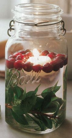 Christmas mason jar decoration: Leaves, cranberries, and a floating candle.