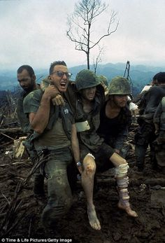 Marines carry an injured soldier back to the medics for treatment following an assault on Hill 484, Vietnam, October 1966