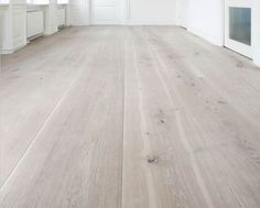 Wide plank flooring with white cabinets and soapstone.