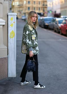 Army green coat, cropped black pants, silver trainers