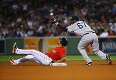 BOSTON, MA - SEPTEMBER 26: Jose Pirela #67 of the New York Yankees drops the ball attempting to tag out Xander Bogaerts #2 of the Boston Red Sox in the ninth inning during their game at Fenway Park on September 26, 2014 in Boston, Massachusetts. (Photo by Al Bello/Getty Images)