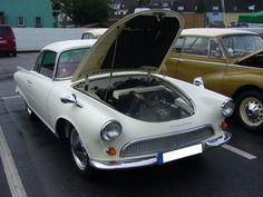Ein DKW Auto Union 1000 Sp Coupe gibt den Blick in seinen Motorraum frei. Das 1000 Sp Coupe wurde auf der Frankfurter Automobil-Ausstellung 1957 vorgestellt. Stilistisch erinnert er ein wenig an den Ford Thunderbird aus dem gleichen Zeitraum. Von 1958 bis 1965 wurden exakt 5.000 Coupes vom Typ 1000 Sp produziert. Die Karosserie wurde übrigens bei Baur in Stuttgart hergestellt. Der 3-Zylinderzweitaktreihenmotor leistet in diesem Modell 55 PS aus 980 cm³ Hubraum.  VAG Gottfried Schultz in…