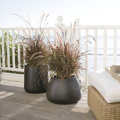 Handsome planters play the supporting role with style, showcasing greenery indoors or out. Curved wide-mouth containers in neutral charcoal grey are cast from an innovative blend of stone, plastic and cement that adds strength while reducing weight.