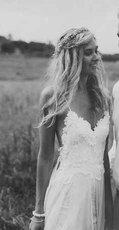 Gorgeous boho/hippie bride with braids, long blond hair, and scalloped white wedding gown in country setting.
