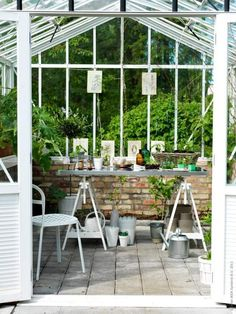 plantes vertes et table de rempotage dans le jardin vitré