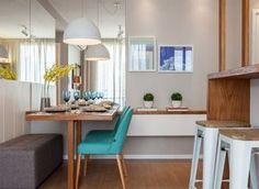 Na sala de jantar, cadeiras azuis, da Oppa Design, dão um toque de cor à base neutra do projeto. O pufe cinza, à venda na Tok&Stok, traz aconchego ao espaço. Pendentes da Só Lustres. Quadros escolhidos na UrbanArts (Foto: Alessandro Giraldi/Divulgação)