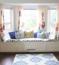 A window seat is one place where, if you are going to opt for curtains, they really do need to be short. A simple treatment will work best here, so as not to distract from the cushions and rug. I would have gone for a striped or geometric pattern, rather than the floral.
