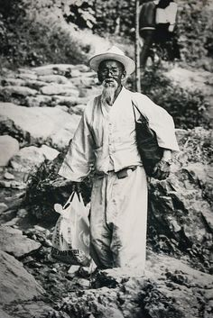 """""""Haraboji"""" (Grandfather) was taken in the Summer of 1986 on Muedeung Mountain, outside Gwangju City, South Korea, by Silverback on Flickr. """"This image has occasionally played though my mind over the years as representative of the rapid change going on in this great nation. …Some of these ideas are shown here with the combination of traditional wardrobe with modern eyeglasses, wrist watch, and plastic bag."""""""