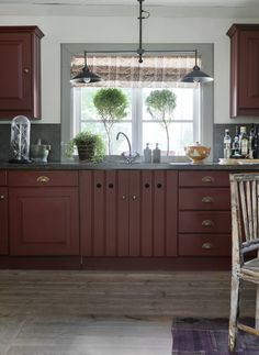 Lantkök med snickerier i engelskt rött. Lampan är belgiskt och keramiken skånsk och Wedgewoodinspirerad.