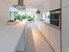 Strakke keuken van met raam boven het aanrecht. Een raam boven je aanrecht kan zorgen voor veel extra licht in de keuken. Daarnaast is het vaak fijner om te werken emt natuurlijk licht. En je kunt lekker naar buiten kijken tijdens het voorbereiden van de maaltijd!