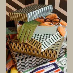 des boîtes en carton peintes au pochoir et au tampon avec des motifs géométrique en noir et blanc et gris colorés comme des carreaux ciment....