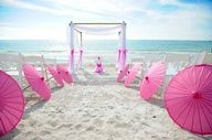 anna maria island beach wedding with pink parasol umbrellas.  One way to keep cool! Very nice!