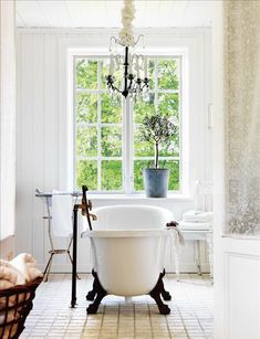 I love this claw foot tub! At least this chandelier has candles...it's ridiculous to put an electrical object where it can fall into water.