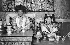 Photographer: Frederick Spencer Chapman, Date of Photo: February 14th 1937, Named Person: Pema Dolkar Tsarong, Region: Lhasa, Tsarong House Tsarong's wife, Pema Dolkar, during the New Year celebrations at Tsarong's house. Wearing ceremonial Lhasa noble dress seated at a table with offering bowls in front of her.