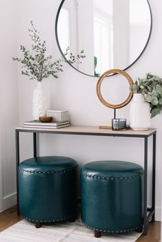 front entry table with round mirror and ottomans