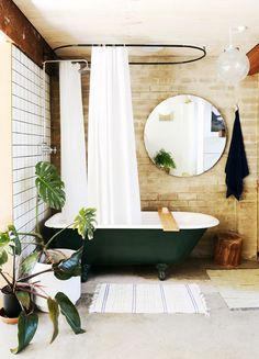 Natural & neutral tone bathroom with green claw foot tub