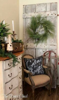 """Text and saying on the pillow """"All is Calm, All is Bright"""" for chalkboard art as well. Love the old barn door and simple wreath. Nice vignette."""