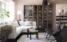 Modern glass-fronted display cabinet in brown ash veneer in a living room.