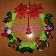 Corona navideña con dos poinsettias y una campanita bordada.