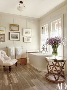 Paintings of Long Island are grouped in Susan's bath | archdigest.com