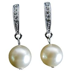 Price $10.99 ERC860 Elegant trendy fashion collection genuine swarovski Ivory Pearl dangling from glittering rhinestones accented surgical post earrings. Wedding party earrings for bridesmaid & flower girls earrings.   Material Used : 10mm Genuine Swarovski Ivory Pearl drop from rhinestones surgical post earrings.  Color : Ivory.  Earrings Length : 1 1/4 inches long.  Earrings Type : Surgical Post Earrings