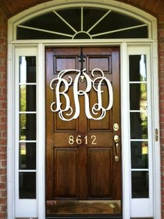 Wooden monograms. Love this simple rich natural wood door with gold numerals.