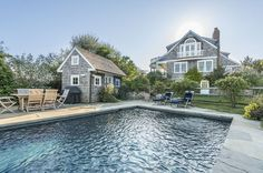 The landscape features a gunite pool, pool house and plenty of manicured lawn.
