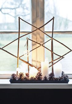 Homemade christmas advent decoration with black candles and large cones.