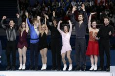 The Canadian team wave to spectators during the flower ceremony as they stand on the podium after they placed second in the team figure skat...